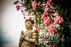 The Statue of buddhism. Picture of buddhism statue and nerium oleander flowe3t Royalty Free Stock Photo
