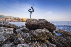 Statue in Budva. Rocky shore of Budva town with small statue of dancing girl in Montenegro Royalty Free Stock Photo