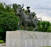 Statue of a bull with big horns and a woman sitting on it stock photos