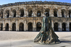 Statue of bullfighter Nimeno II and Roman amphitheater in Nimes, Royalty Free Stock Image