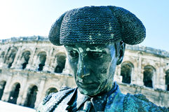 Statue of bullfighter Nimeno II and Roman amphitheatre in Nimes, Stock Image