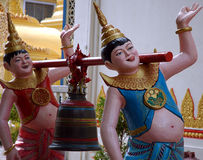 Statue in Burmese Temple. 2 statue carying a bell in a burmese temple stock photo
