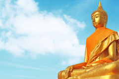 Statue of Buudha with  sky background. Glold statue of Buudha with blue sky background Royalty Free Stock Photography