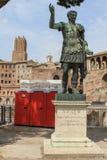 Statue CAESARI NERVAE Augustus, Rome, Italy. Statue S.P.Q.R. IMP.CAESARI NERVAE Augustus on street Via dei Fori Imperiali in front of public toalets, Rome, Italy Stock Photos