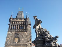 Statue on Charles bridge with tower in background. In Prague royalty free stock photo
