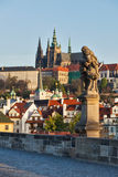 Statue on Charles Brigde against St. Vitus Cathedral in Prague Stock Photos