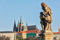 Statue on Charles Brigde against St. Vitus Cathedral in Prague Royalty Free Stock Image