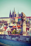 Statue on Charles Brigde against St. Vitus Cathedral in Prague Stock Image