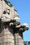 Statue che tengono le lampade sferiche nella stazione ferroviaria di Helsinki immagini stock