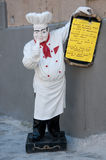 Statue of chef holding a menu of a restaurant. Italy Stock Image