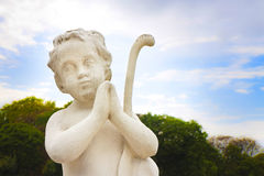 Statue of a cherub praying against blue sky Royalty Free Stock Photography