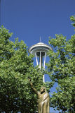 This is a statue of Chief Seattle in front of the Space Needle. There is green summer foliage on the trees surrounding the statue. Stock Photography