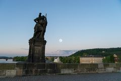 Statue of Child Christus at the shoulder of saint Christopher, Charles bridge. Prague during early morning with full moon as background stock image