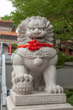 Statue chinoise de lion avec le ruban rouge Photographie stock libre de droits