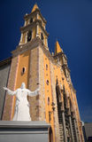 Statue of Christ in front of Mazatlan Church. White statue of Jesus in front of the orange cathedral church in Mazatlan stock image