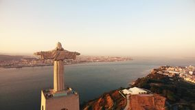 Statue Christ the King Cristo Rei Lisbon Almada at sunset aerial view stock video footage