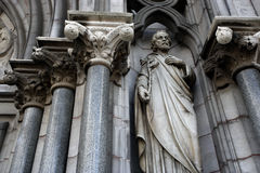 Statue on church exterior. Low angle view of biblical statue of man on exterior of stone church stock images