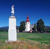 Statue and church in Liptovske Matiasovce stock images