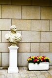 Statue on a column and flowers Stock Photo