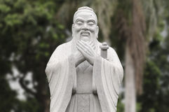 Statue of Confucius. Stone statue of Confucius with blurred trees background Stock Photo