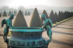 Statue contro il contesto al giardino del palazzo di Versailles immagini stock libere da diritti