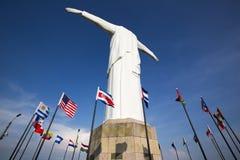 Statue Cristo Del Rey von Cali mit Weltflaggen und blauem Himmel, Col. Stockfotos
