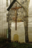 Statue of crucified Jesus built over a wall with a homage spot below it Royalty Free Stock Photos