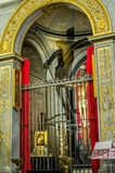 Statue of the crucifixion of Jesus Christ among the icons at the altar on which is reflected shadow on the wall of the temple in t. Statue of the crucifixion of stock images