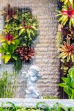 Statue of Cupid in cozy garden. Statue Cupid and waterfall in cozy garden on summer Royalty Free Stock Photos