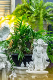 Statue of Cupid in cozy garden. Statue Cupid and waterfall in cozy garden Stock Photography