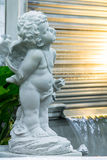 Statue of Cupid in cozy garden. Statue Cupid and waterfall in cozy garden Royalty Free Stock Photos