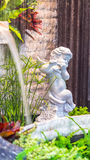 Statue of Cupid in cozy garden. Statue Cupid and waterfall in cozy garden Stock Images