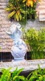 Statue of Cupid in cozy garden. Royalty Free Stock Photos