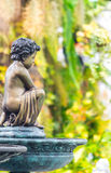 Statue of Cupid in cozy garden. Royalty Free Stock Photography