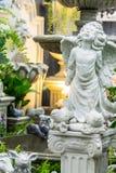 Statue of Cupid in cozy garden. Stock Images