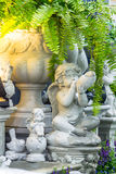 Statue of Cupid in cozy garden. Statue Cupid and waterfall in cozy garden on summer Royalty Free Stock Images