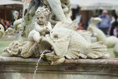 Statue of Cupid and fish from the fountain of Neptune Royalty Free Stock Images