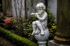 Statue of Cupid playing the flute Royalty Free Stock Image