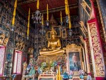 Statue d'or de Bouddha avec la peinture murale antique autour Photos stock