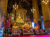 Statue d'or de Bouddha dans le trône et dans le temple avec de grandes colonnes Photos stock