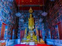 Statue d'or debout de Bouddha dans le temple avec la peinture murale Images libres de droits