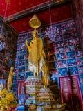 Statue d'or debout de Bouddha dans le temple avec la peinture murale Image libre de droits