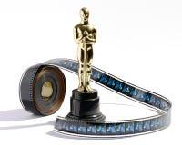 Statue d'oscar de reproduction avec un rouleau de pellicule cinématographique Photos libres de droits
