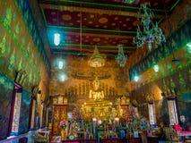Statue d'or thaïlandaise de Bouddha dans le temple avec la peinture murale Photographie stock libre de droits