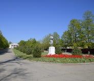 Statue d'un agriculteur collectif sur un piédestal Le legs de l'ère soviétique Un lit de fleur avec des tulipes et de jeunes arbr images stock