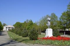Statue d'un agriculteur collectif sur un piédestal Le legs de l'ère soviétique Un lit de fleur avec des tulipes et de jeunes arbr photographie stock libre de droits