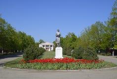 Statue d'un agriculteur collectif sur un piédestal Le legs de l'ère soviétique Un lit de fleur avec des tulipes et de jeunes arbr photographie stock