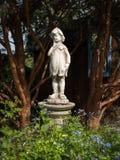 Statue d'un garçon fait en pierre se tenant dans un jardin photos libres de droits