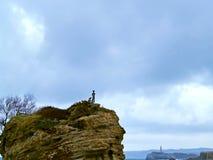 Statue d'un garçon sur une roche en mer image stock