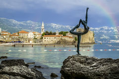 The statue of a dancing girl on a background of the old town of Stock Image